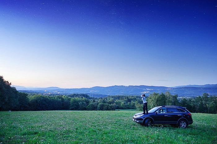 ženska stoji na avtomobilu na gozdi jasi in tuli (izvaja howling)