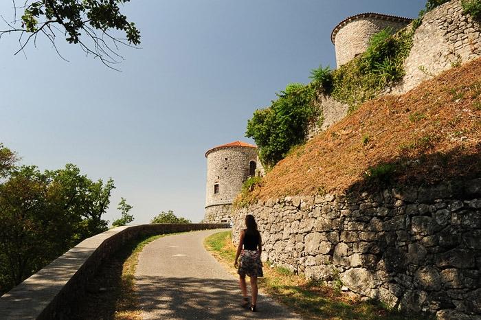 ženska hodi po cesti proti gradu. grad rihemberk