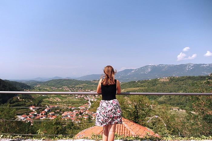 ženska stoji ob ograji, pod njo razgled na Vipavsko dolino