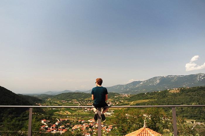 moški sedi na ograji gradu Rihemberk, pod njim vipavska dolina