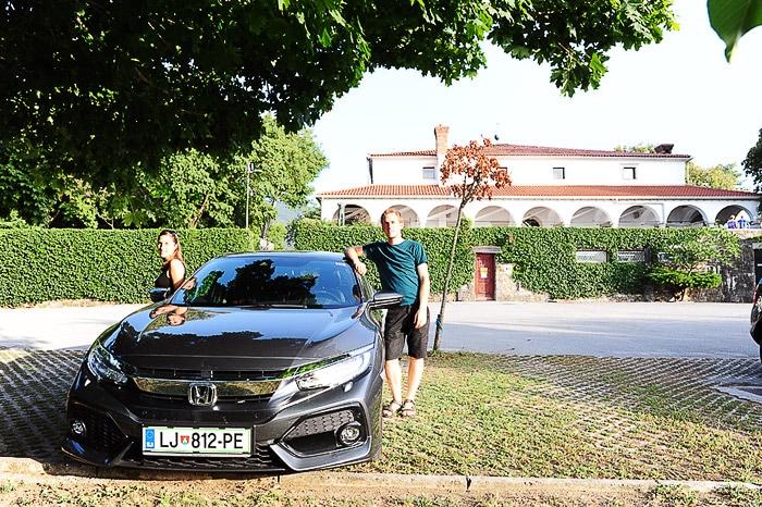 moški in ženska stojita ob avtomobilu Honda Civic, v ozadju dvorec Zemono