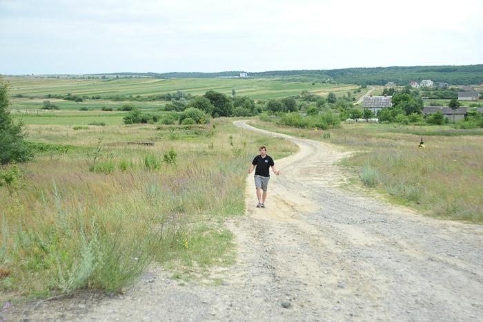 moški hodi po makadamski cesti sredi polja. Ukrajina