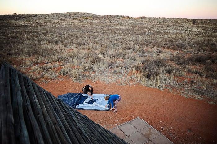 moški in ženska postavljata šotor v safari parku Kgalagadi