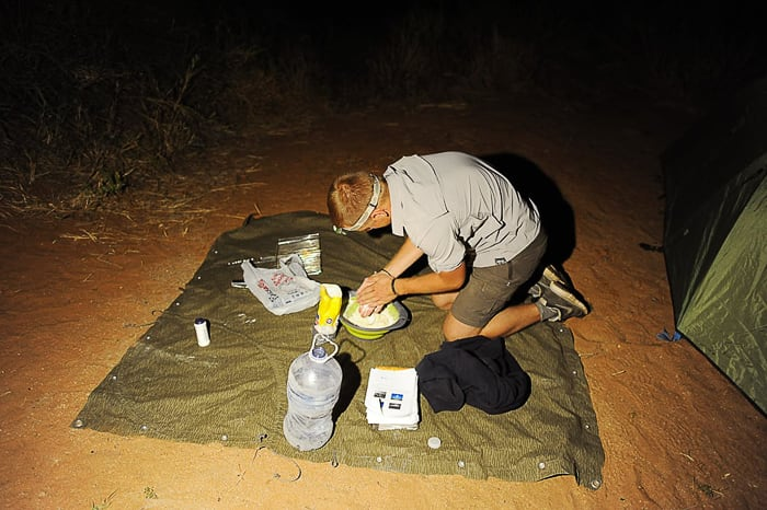 moški na šotorskem platnu pripravlja večerjo