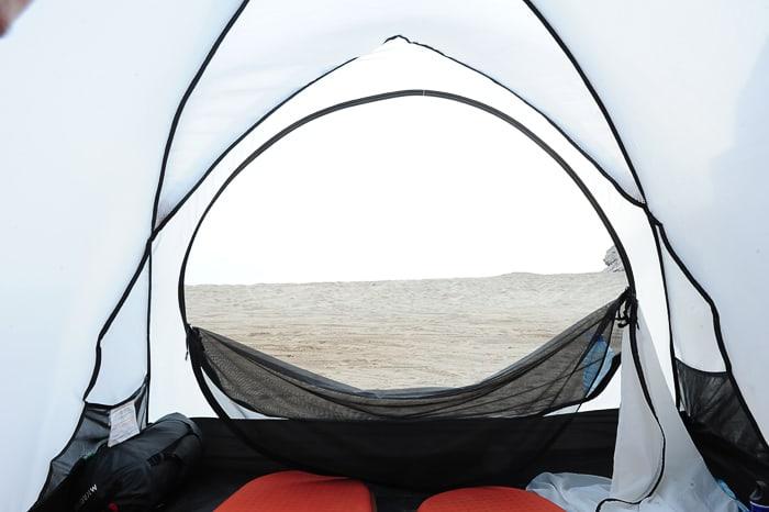 pogled na peščeno plažo iz belega šotora