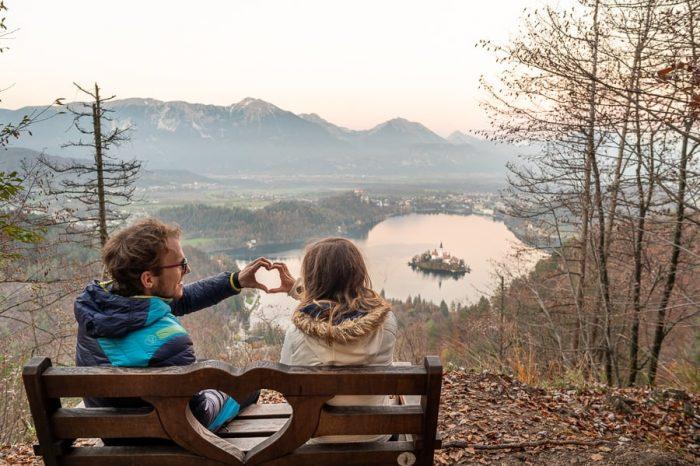 klopca ljubezni nad Bledom. Moški in ženska sedita na klopci z izrezljanim srcem