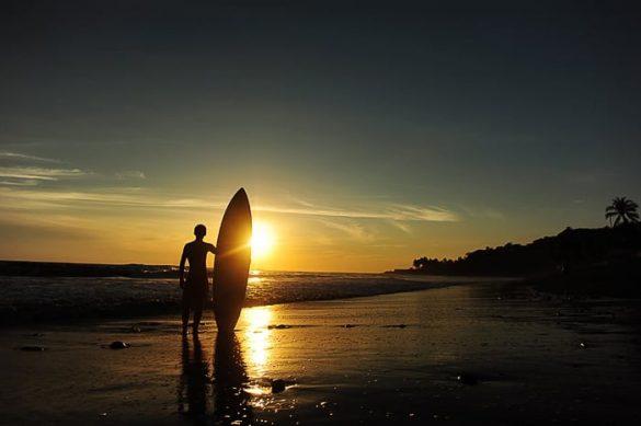 moški s surfom ob sončnem zahodu