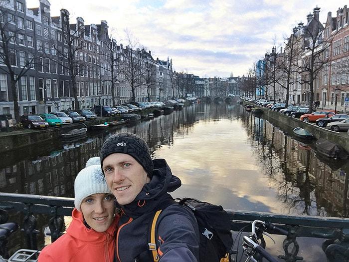 moški in ženska ob kanalu v Amsterdamu