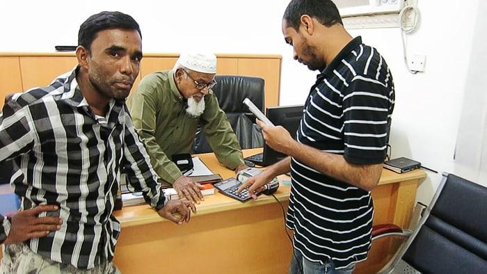 v pisarni v Omanu: omanski moški v tradicionalni obleki in dva indijska pomočnika