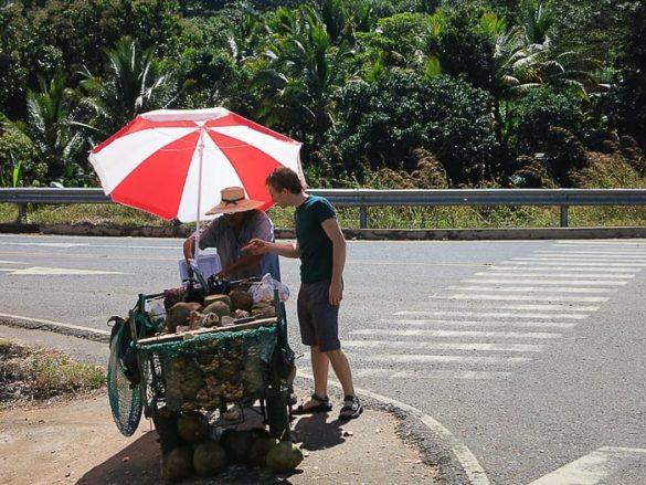moški kupuje kokos na stojnici ob cesti Salvador