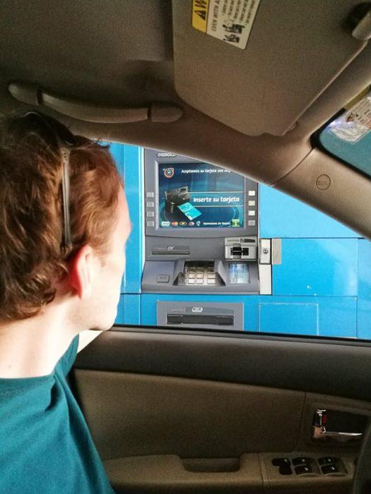 moški dviguje denar na drive thru bankomatu