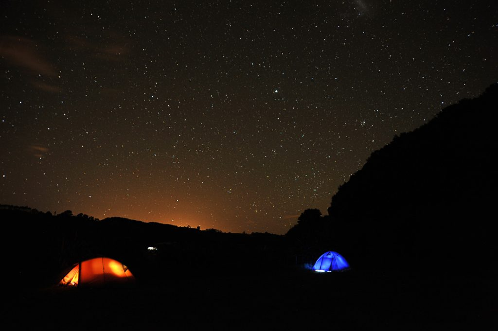 dva osvetljena šotora v temni noči sredi Nove Zelandije
