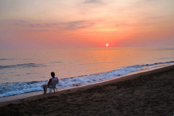 Rok, ki opazuje sončni zahod na plaži Porto Katsiki, Lefkada