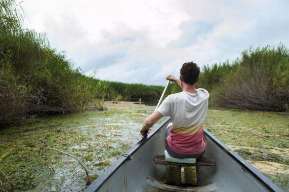 človek v kanuju pluje po reki