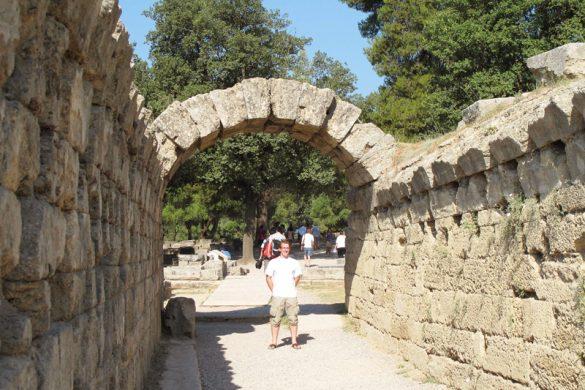 moški stoji ob antičnim kamnitim obokom, Grčija