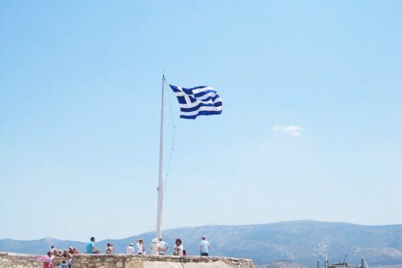 grška zastava plapola nad antičnimi ostanki