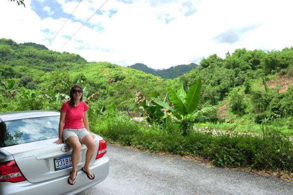 Ženska sedi na avtomobilu, v ozadju je bujno tropsko rastje