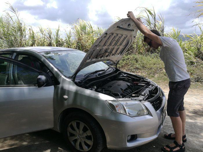 odprt pokrov avtomobila in Rok, ki gleda notri. Najem avta na Jamajki se ne splača