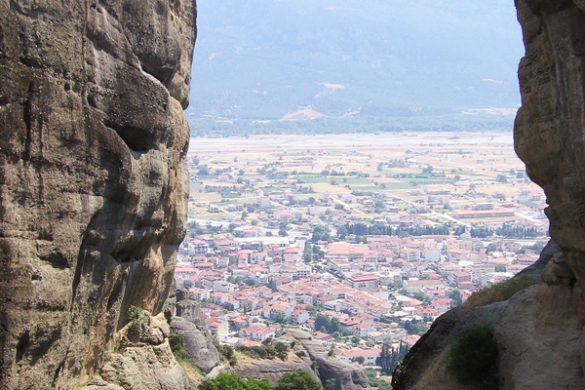 pogled na mesto v dolini skozi špranjo med dvema skalama