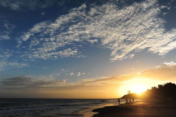 ljudje, ki hodijo po plaži ob sončnem zahodu