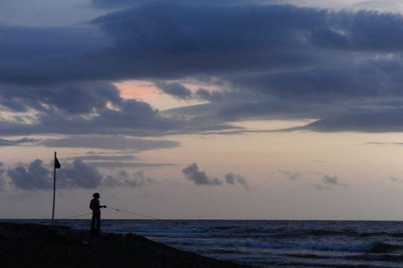 ribič ob sončnem zahodu na plaži Bull Bay, Jamajka