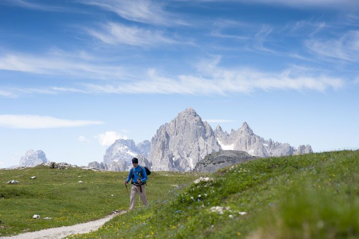 Pohodnik hodi po travniku v Dolomitih, v ozadju so gore. Vzpon na Oberbachernspitze, ena izmed 3 ture v Dolomitih, ki jih lahko prehodi vsak