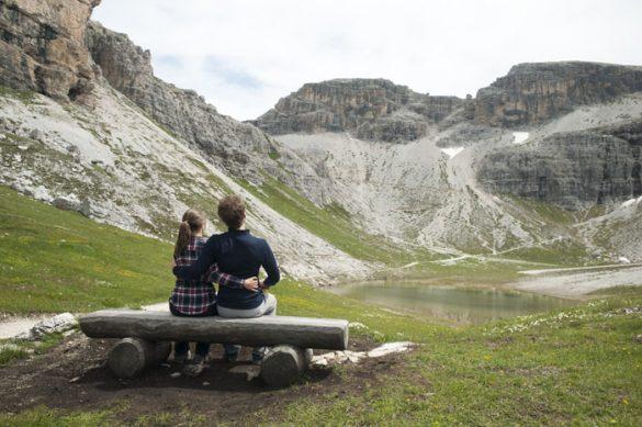 moški in ženska na klopi pod gorami, Dolomiti