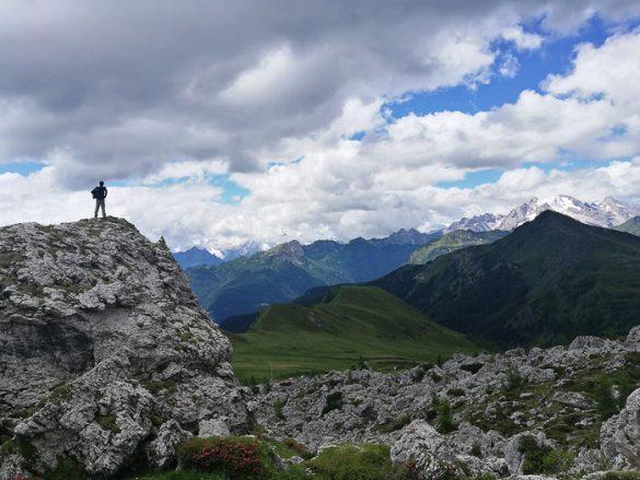 Pohodnik na razgledni skali, v ozadju je Marmolada, Dolomiti