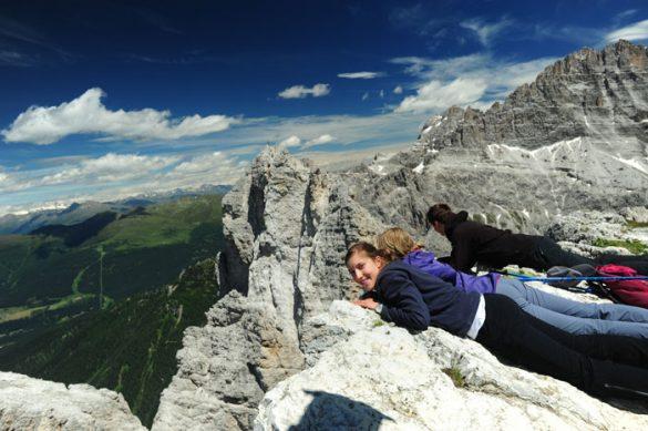 Ženska leži na vrhu hriba in gleda v prepad