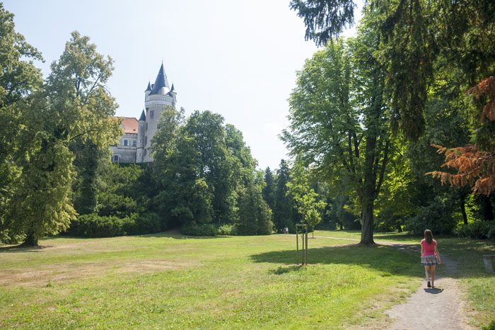 ženska se sprehaja po parku okoli gradu Žleby