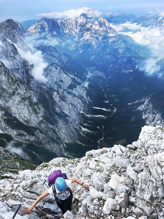 ženska pleza po skali Alpe, zadaj razgled na dolino Trente