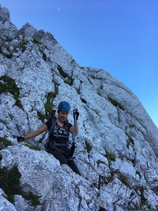 Alpinistka s čelado in samovarovalnim kompletom v steni