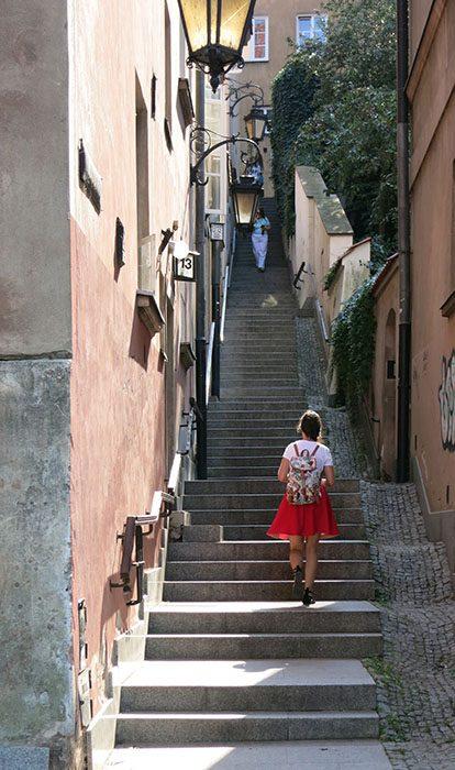 ženska hodi po stopnicah starega mestnega jedra Varšave