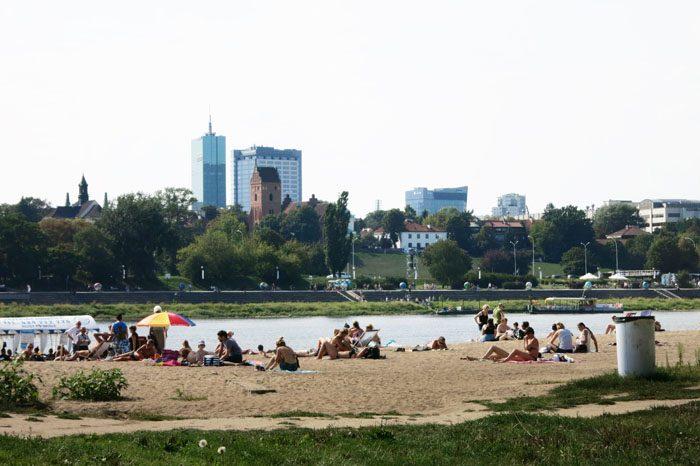 ljudje se kopajo in sončijo ob reki Visli