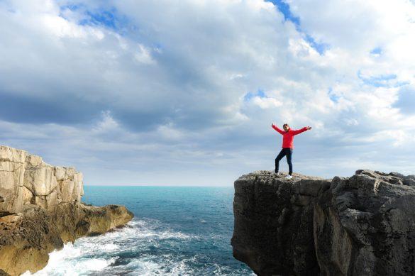 ženska na vrhu skale nad morjem