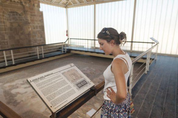Ženska bere tablo z opisom turistične znamenitosti Paphos Ciper