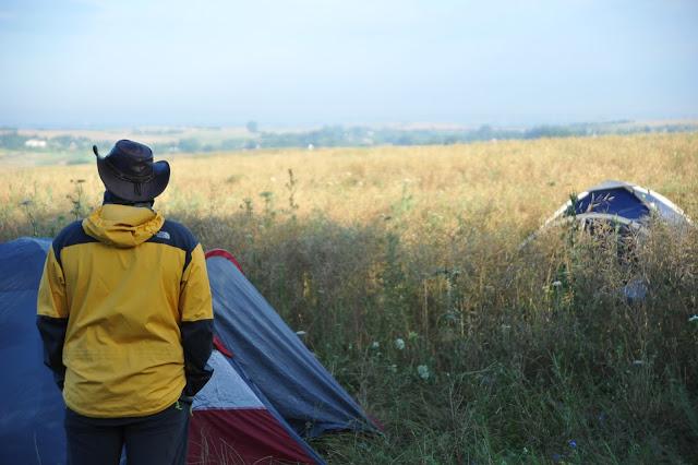 moški s klobukom stoji na robu žitnega polja ob svojem šotoru