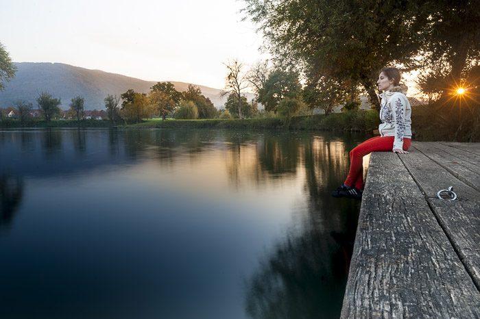 Ženska sedi na obali reke in opazuje sončni zahod v Kostanjevici na Krki