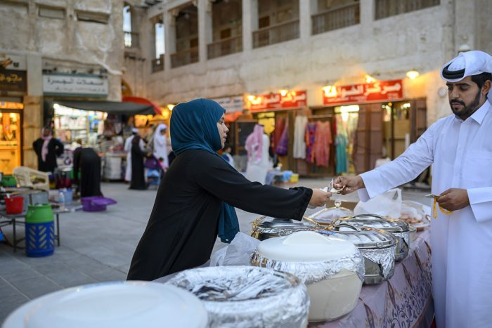 muslimanska ženska ponuja domačo arabsko hrano na Souq Waqif