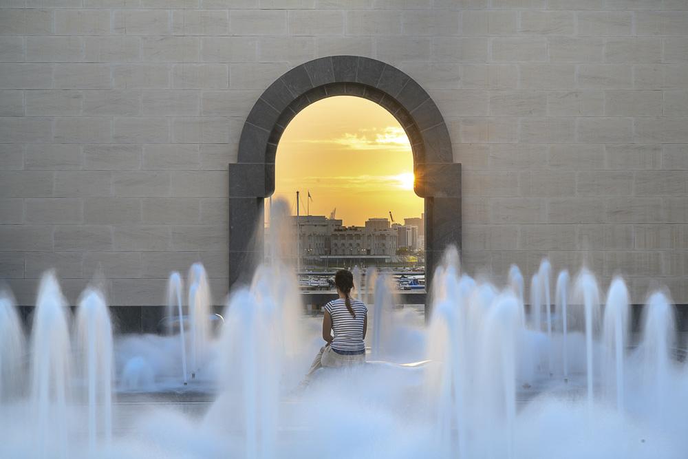 ženska opazuje sončni zahod pred muzejem islamske umetnosti, Doha