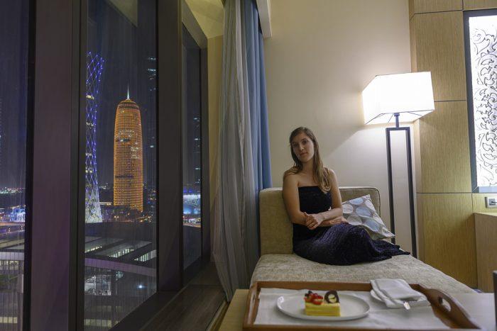 Ženska v hotelski sobi s pogledaom na Doho