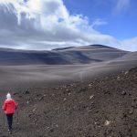 Ženska pohodnica v črni pokrajini pod vulkanom