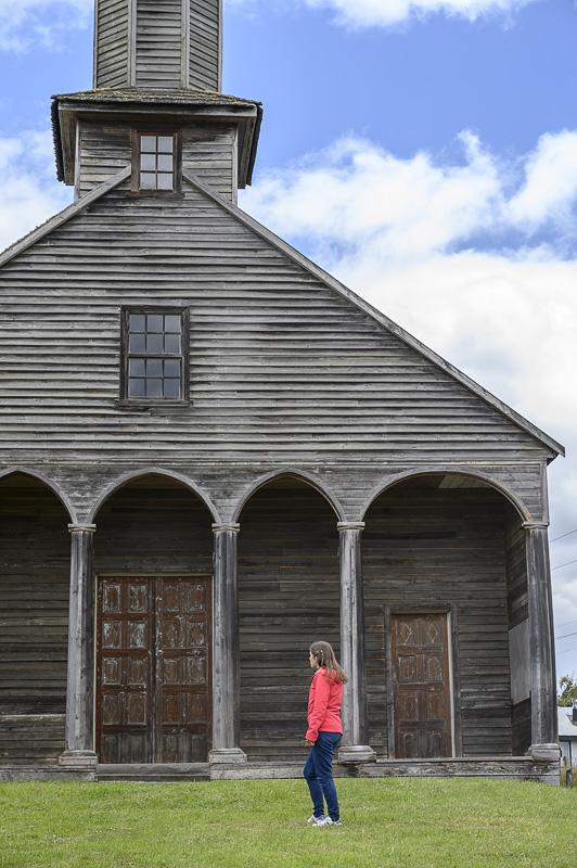 ženska pred leseno cerkvijo na otoku Chiloe