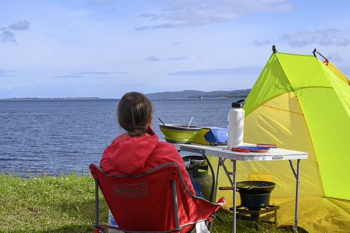 ženska pred šotorom gleda na morje