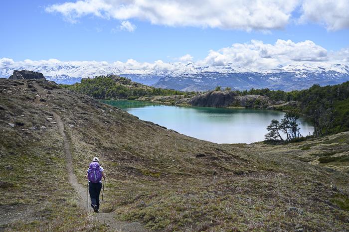 ženska hodi ob jezeru s pogledom na gore Ande