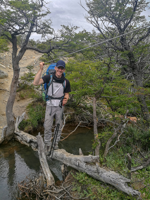 Moški na leseni brvi prečka reko