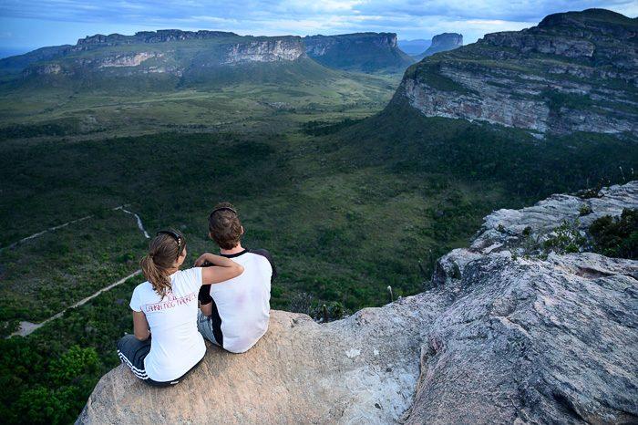 moški in ženska sedita na skali nad dolino. Chapada Diamantina, Brazilija