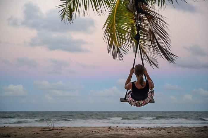 ženska na gugalnici pod palmo. peščena plaža v ozadju.