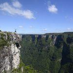 moški stoji na vrhu kanjona Serra Geral