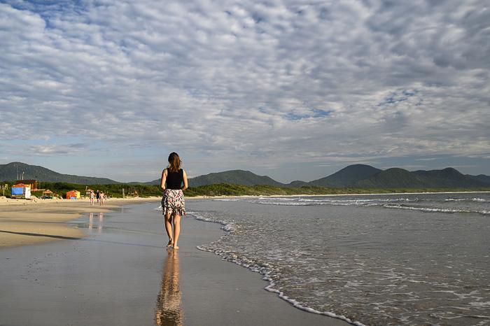ženska v poletni obleki hodi po plaži